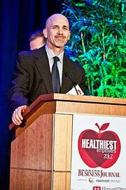Rick Riess, director of behavior medicine at Health Management Resources, accepts their award in the small company category at the Boston Business Journals Healthiest Employers awards breakfast.