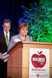 Susan Potvin, director of quality improvement at Family Service Association accepts their award in the medium company category at the Boston Business Journals Healthiest Employers awards breakfast.