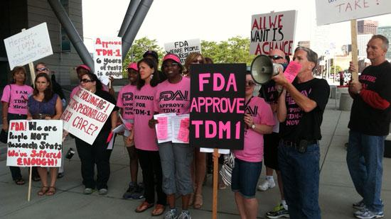 Protesters outside the BIO conference in Boston called on the FDA to expedite approval of TDM1, a potential drug cancer therapy developed by Immunogen and Genentech.