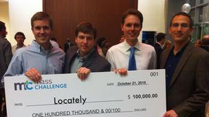 Locately team accepting an oversized check from MassChallenge