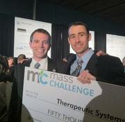 Therapeutic Systems co-founders Chris Leidel (left) and Brian Mullen hold up their giant, $50,000 check from MassChallenge.