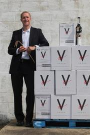 Paul Kozub with cases of his V-One Vodka.
