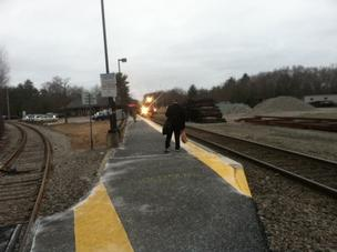 Walpole Station A lone commuter stands on the platform at Walpole Station as the 7:54 a.m. the train into Boston approaches. The waiting area is usually lined, several people deep for the morning commute.