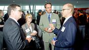 Comcast's Tim Murnane, Doreen Vigue and Steve Hackley speak with Ed Barker of Earthwatch at the Boston Business Journal's Best Places To Work award breakfast held at the BCEC.