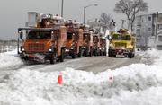 Utility trucks sit idle along Winthrop Shore Drive after Winter Storm Nemo in Winthrop, Massachusetts, U.S., on Saturday, Feb. 9, 2013.
