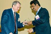 Kirk Davis of Gatehouse Media which was an event partner of the Massachusetts Business Climate Summit presents one of the three awards to companies who grew jobs in Massachusetts over the last three years to Girish Navani, founder and CEO of eClinicalWorks.