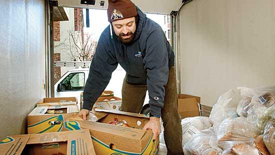 Jeremy Zeitlin, a haul manager for Lovin' Spoonfuls, loads up food such as fruit, vegetables and bread donated from a local grocery store.