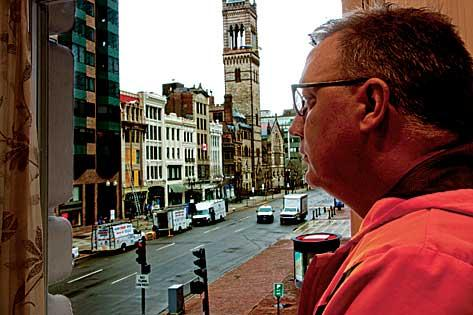 Daniel Donahue, the managing director of The Lenox Hotel, peers out from a hotel room at the site of the Boston Marathon bombing on Boylston Street.