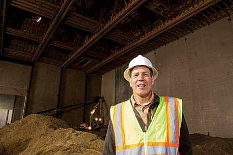 Michael Meyers, director of real estate for the New England Studios project that's being built in Devens, stands below some of the complex's Douglas fir trusses — each 120 feet long, 16 feet high and 40,000 pounds.