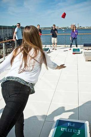 Employees at fama PR  play Baggo — a bean bag game — on the sun deck at the company's Liberty Wharf location.