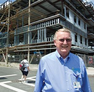Photo of East Boston Community Health Center CEO Jack Cradock standing in front of a building under construction.