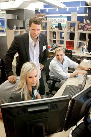 CEO of FreeCause Michael Jaconi, standing, along with employees Corinne Salchunas and Ryan Cole, have been part of a company-wide effort to learn software coding.