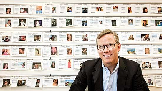 Brian Halligan, co-founder and CEO of HubSpot, in front of a wall of employee profiles. The fast-growing company has nearly 400 employees in Cambridge.