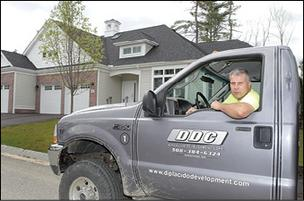 Contractor Thomas DiPlacido, at the Norfolk condominiums he built, is among business owners benefiting from banks' willingness to lend again.