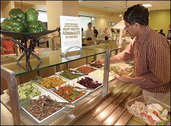 Tufts Health Plan employee Rao Ponduru samples some of the healthy food choices in Tufts on-site cafeteria. Tufts is a finalist in the Healthiest Employers large company category.