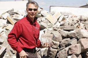 Scott Smith holds a piece of cobblestone in front of a giant pile from which stones and debris have been separated. He said many durable pavement bricks, such as the one at right, are 100 years old and have withstood pounding from traffic, street resurfacing and road salt.
