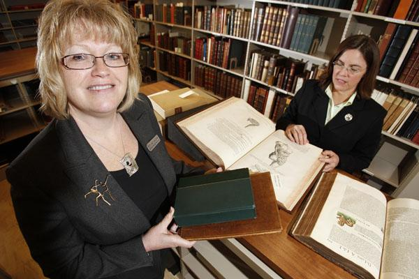 """Mary Jean Jakubowski, left, Buffalo and Erie County Public Library director, and Amy Pickard, rare book librarian, examine the Milestones of Science collection. The green book in the director's hands is a first edition of Darwin's """"The Origin of Species."""""""