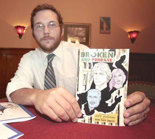 "Mark Pogodzinski, an author and now a publisher, displays a copy of ""Broken and Profane,"" one of the titles issued by No Frills Buffalo."