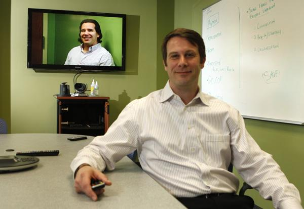 Demonstrating videoconferencing equipment at the Amherst office is VoIP Supply LLC CEO Benjamin Sayers, seated, and chief marketing officer Garrett Smith, who will oversee the new division. Sayers is hopeful the emphasis on such systems could result in revenues doubling in two years.