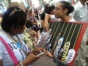 Vendors hawk buttons on the streets of uptown during Monday's CarolinaFest.