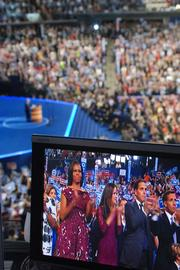Michelle Obama is seen on TV screens as she listens to Vice President Joe Biden's speech from a row of seats directly in front of the stage at Time Warner Cable Arena.