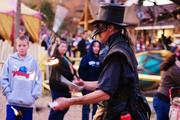 The Raven performs his fire-juggling act among the crowd. The Carolina Renaissance Festival employs some 500 costumed actors for each festival day, with some performing on the fair's 11 stages and some walking among revelers.