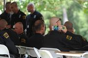 At the Charlotte Mecklenburg Police and Fire Training Academy, officers arriving from other cities gathered Saturday under a white tent for lunch. Here an officer cools himself with a chilled water bottle.