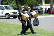 At the Charlotte Mecklenburg Police and Fire Training Academy, officers from other cities congregate to help out during the DNC. Here they carry boxes with helmets they will wear while handling crowd control.