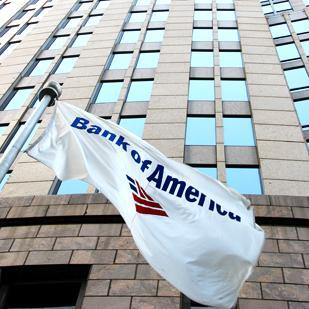 A company flag flies outside Bank of America's headquarters in Charlotte. The bank says it is selling its foreign credit-card operations.