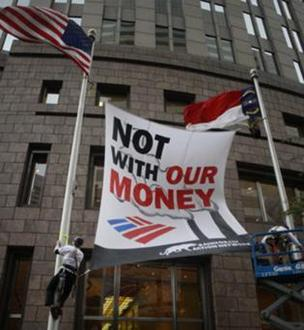 Protesters demonstrated by hanging a banner on Bank of America's flagpoles Tuesday morning in uptown Charlotte.