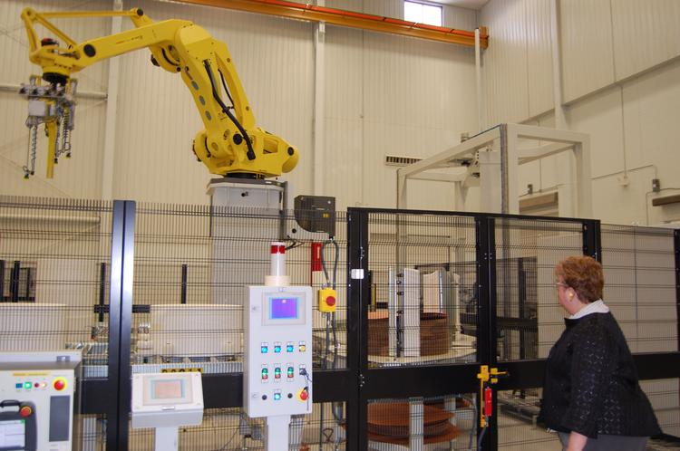 A robotic arm moves spools of nonwovens at Companhia Providencia last week in Statesville.