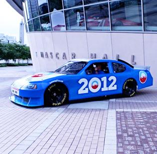 "Democratic National Convention organizers debuted the official ""Powered by the American People"" stock car for the 2012 Democratic National Convention on Friday at the NASCAR Hall of Fame. The blue and white Dodge Charger is emblazoned with the names of 3,502 ""sponsors"" — donors that sent in contributions of $5 or more for the convention."