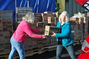 Girl Scout volunteers load cookie boxes into waiting vehicles.