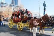 The Wells Fargo stagecoach rolls through uptown Charlotte in the 2012 Belk Carolinas Carousel Parade, decorated for Christmas and carrying a turkey.