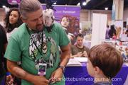An exhibitor shows his life-like puppet to children in the crowd.