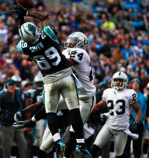 Carolina Panthers wide receiver Steve Smith can't quite make an acrobatic catch over defender Michael Huff during a Dec. 23, 2012, game vs. the Oakland Raiders at Bank of America Stadium in Charlotte.