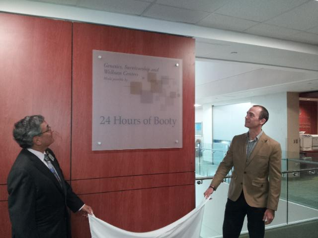 Dr. Derek Raghavan (left), president of Levine Cancer Institute, and24 Hours of Booty founderSpencer Lueders unveil a sign at the cancer institute in recognition of a $1 million gift to the center.