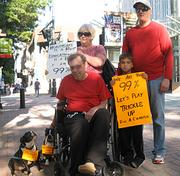 The Davidson family of Huntersville joined Occupy Charlotte demonstrators outside Bank of America headquarters in uptown Saturday. Rick Davidson, who was disabled by a stroke and is a survivor of pancreatic cancer, was accompanied by his wife, Vera, son Kyle, grandson Donovan Martin and dogs Buddy and Buster.
