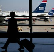 US Airways operates its largest hub at Charlotte Douglas International Airport. The effects of the merger on the local operation won't be clear for a while, but members of the region's business community think the deal is a good one for the city.