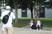 Children pose with the statue of late Panthers player Sam Mills.