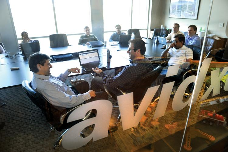 AvidXchange CEO and co-founder Mike Praeger, at left, leads a team meeting at the e-payment company's headquarters in the Metropolitan complex in midtown.