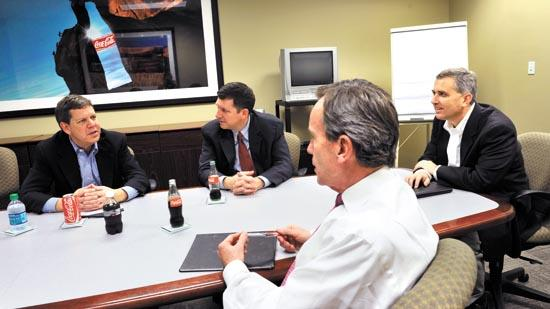 Robin Lyle, president of N.C. Bank & Trust (foreground) is drumming up new business outside real estate development, which used to be a key part of local banking. Here he meets with a client, Coca-Cola Bottling Co. Consolidated. From left: Trip Deal, treasurer at the Charlotte bottler; fellow banker Cutter Davis; and Mark Byers, Coca-Cola Consolidated's senior director of risk management.