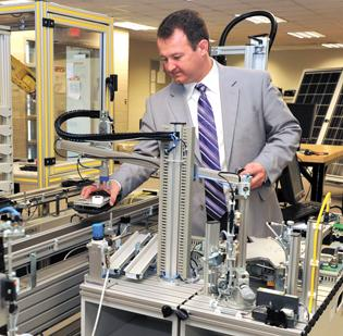 Chad Ray, dean of CPCC's STEM program, touts the intricate equipment in the college's mechatronics labs for its state-of-the-art technology and real-world applications for students.