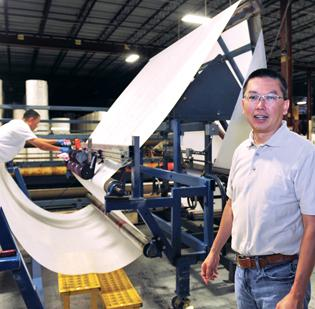 Oxco Inc. of Charlotte resizes and treats nonwoven materials made by other companies. This is a folding machine that imprints and folds material to a customer's specification. The machine was developed by Oxco. At right is company President C.T. Chu.