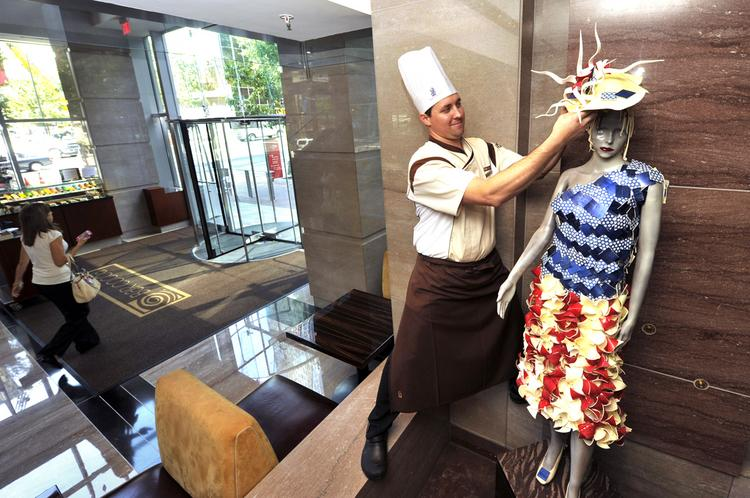 "Ritz-Carlton Pastry Chef Joshua Cain places a hat on ""Madame Cocoa"" in the hotel's Bar Cocoa. He designed the red, white and blue flag chocolate dress she is wearing for the DNC."