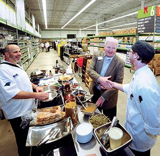 Bob Stout (center), southeast region president of US Foods, visits with chefs John Morey (left) and Patrick McElhiney at the company's CHEF'STORE on Eastway Drive.
