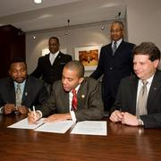 At the agreement signing were, seated from left to right, Evans Nwankwo, Christoper Smitherman, Ken Jones, and standing Willie Carden and Jim Clingman.
