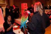 A guest hears about the scarlet macaw from a handler from the Cincinnati Zoo and Botanical Garden.