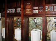 A graffiti-covered segment of the oppressive wall that once separated East and West Berlin now serves an appropriate function in the gentlemen's restroom in the main casino area, as it holds the urinals.  Located at Main Street Station Casino in Las Vegas.