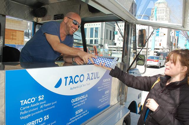 Taco Azul owner and operator, Gary Sims, hands an order to a customer.